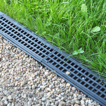 drainage system cover alongside gravel walkway and green lawn